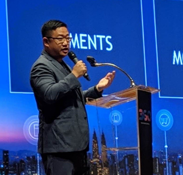 CEO Don Guo sharing about the benefits of blockchain at a tech conference in Cambodia